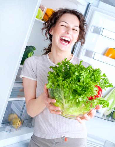 Organizarea frigiderului femeie cu verdeață în mână