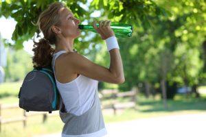 Hidratarea în timpul alergării femeie care bea apă la umbră