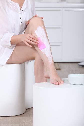 Crema depilatoare femeie care are cremă pe picioare