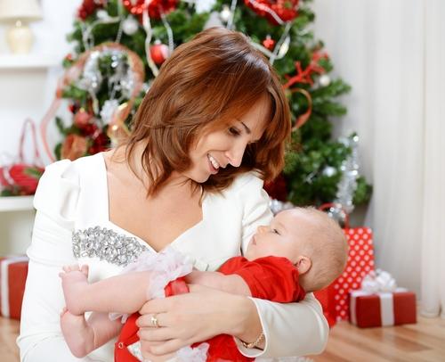 Mama cu bebelus in fata bradului