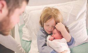 fratele mai mare strânge în brațe bebelușul